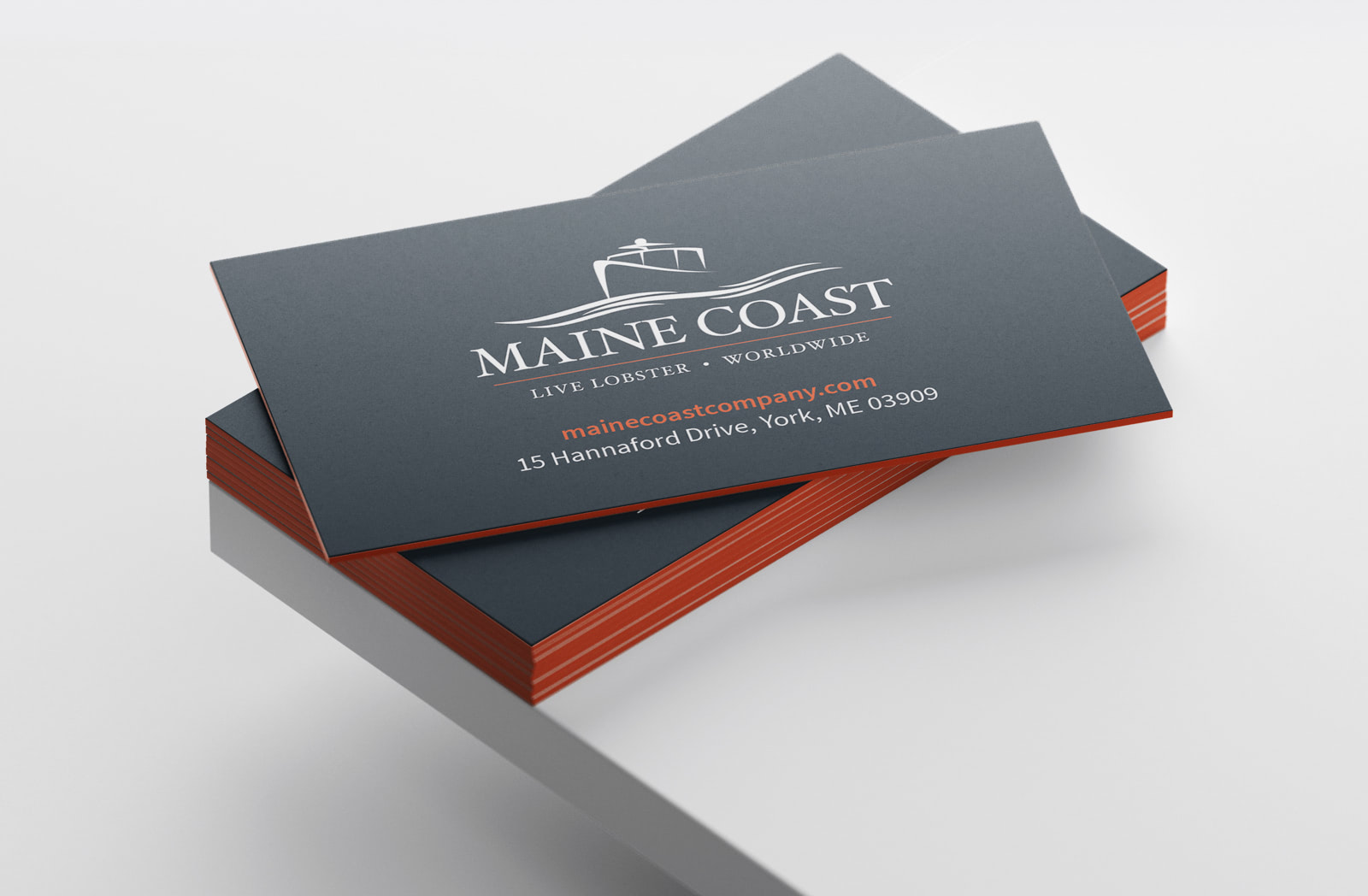 Mockup of a stack of Maine Coast business cards with their logo, website and address on the front and thick, orange painted edges.