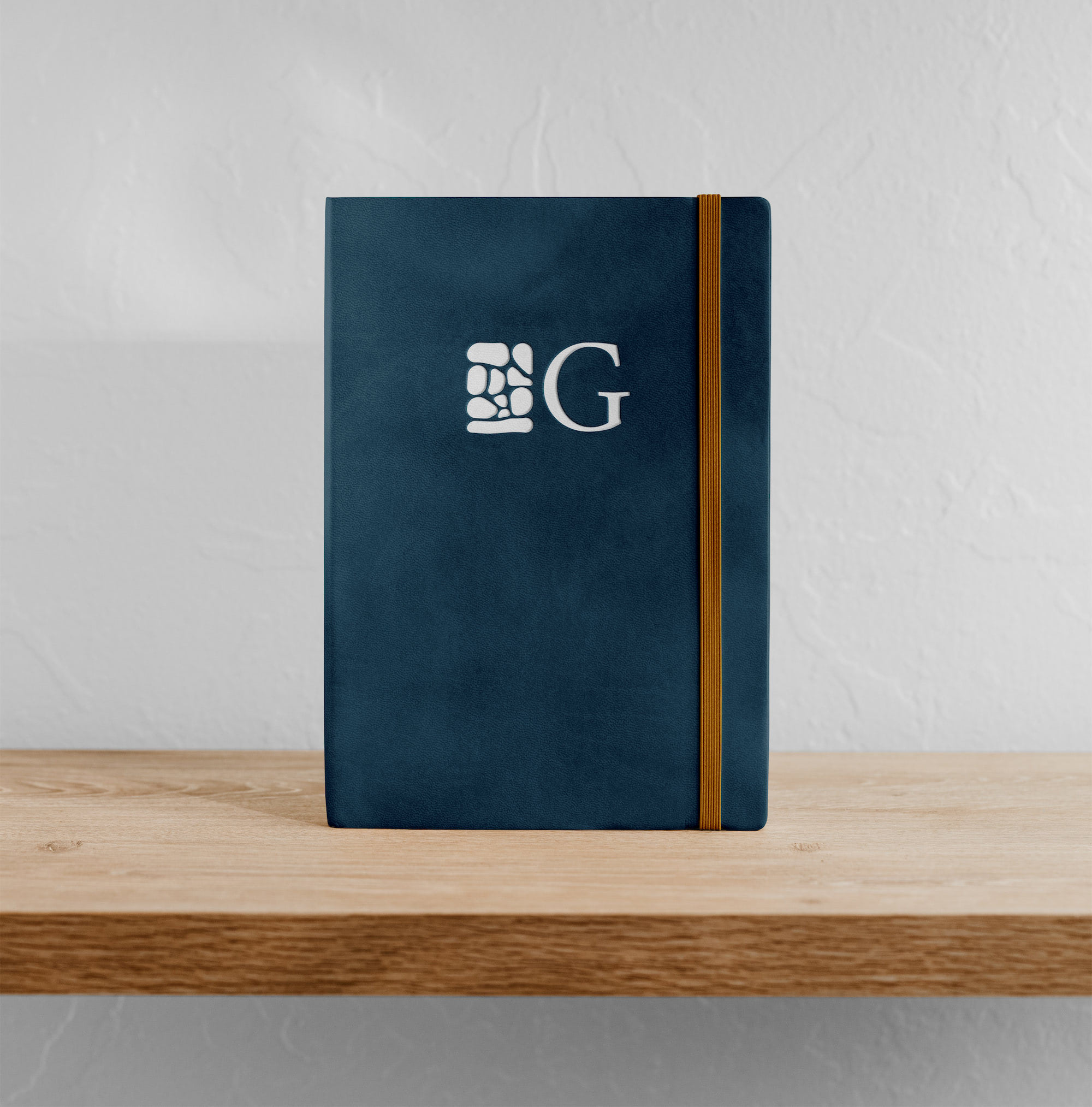 Gather Financial™ Planning logo submark with stone mark and letter 'G' mocked up on a leather bound notebook