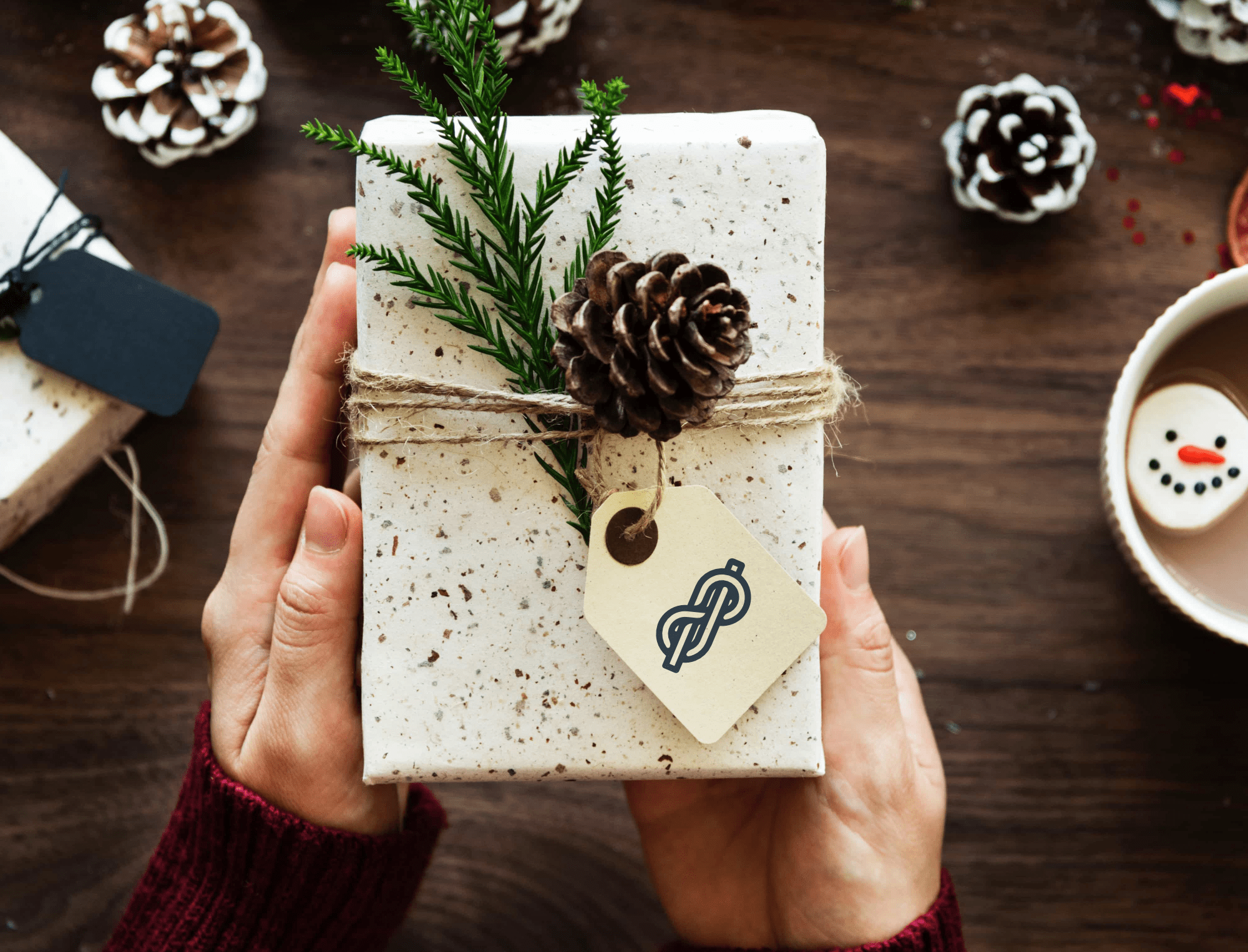 Gift wrapped in marble speckled paper tied with twine with a paper tag, pine tree branch and a pine cone