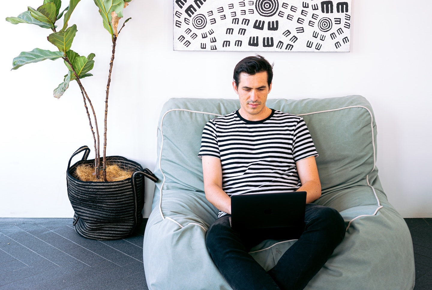 Man sitting on a plush bean bag chair next to an indoor plant while working on his laptop