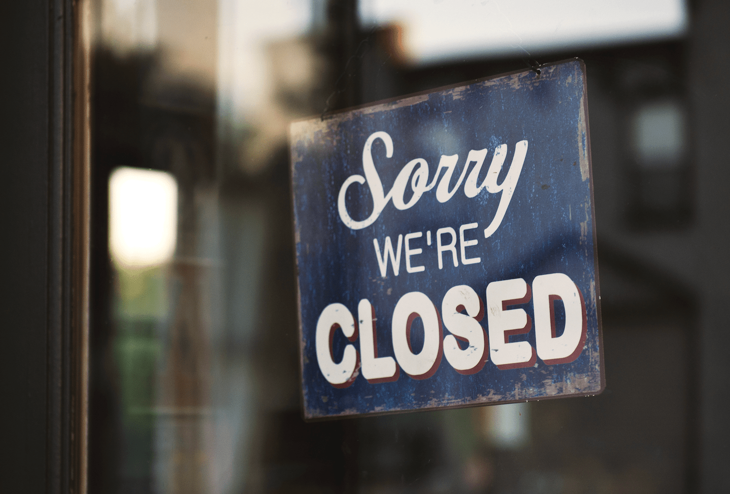 """""""Sorry, we're closed"""" sign in a storefront window"""