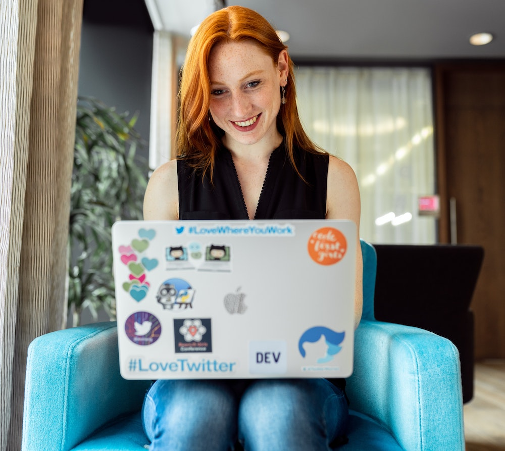 Person smiling while using a laptop in a comfortable setting.