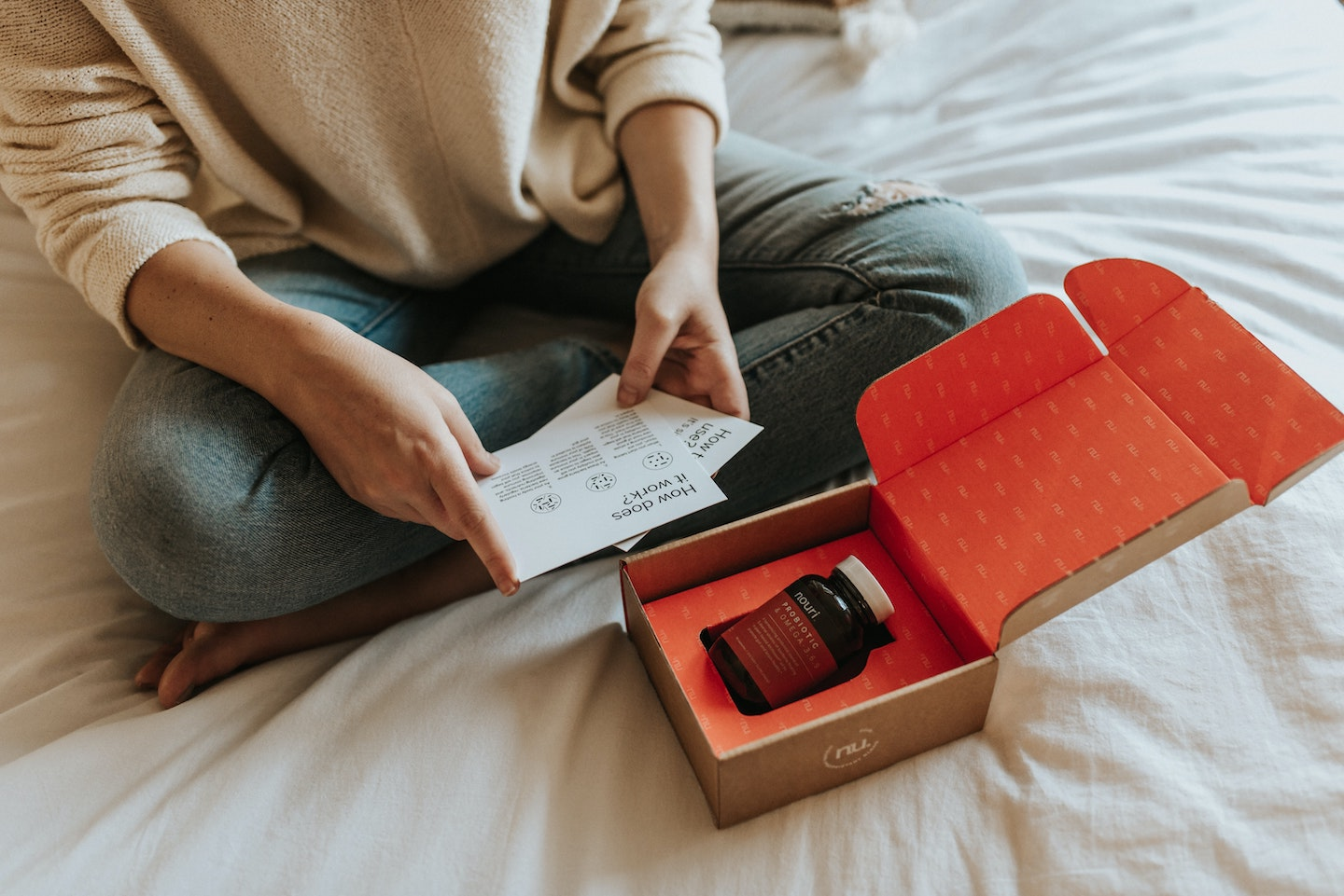 person sitting on bed holding informative post cards with an open box