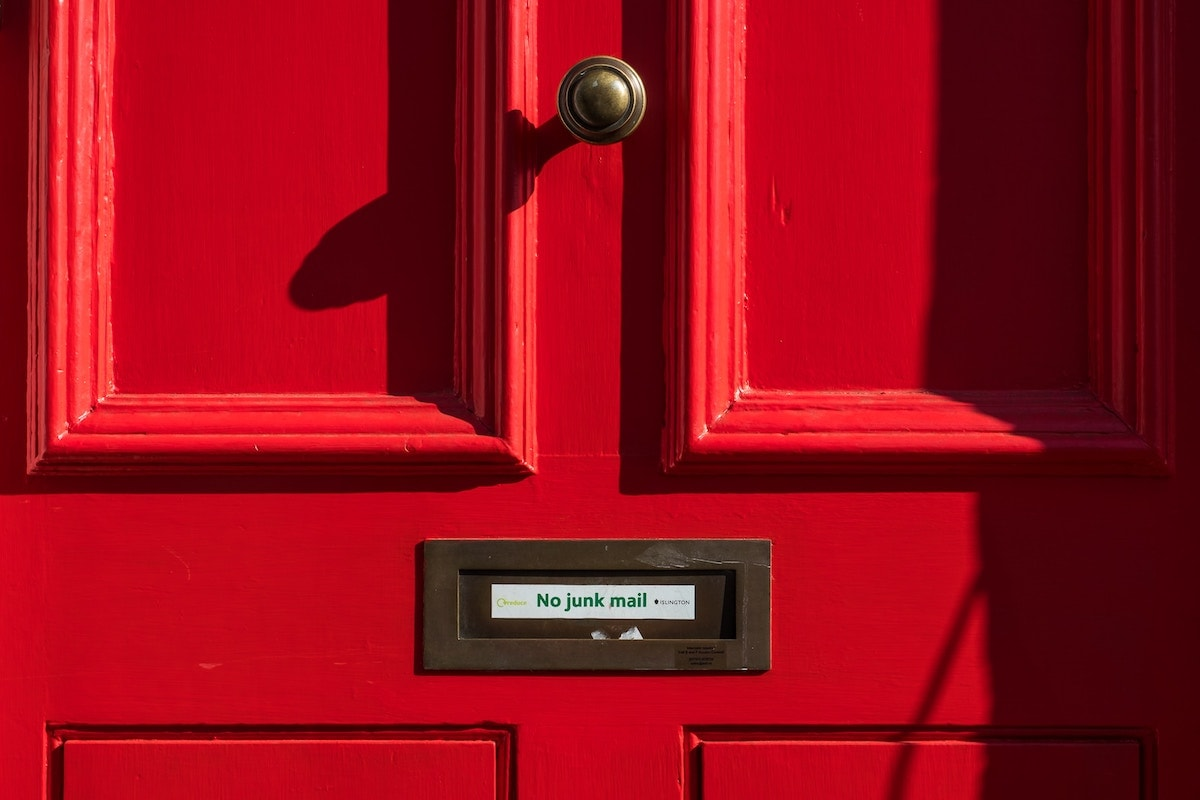 Red wooden door with mail slot that reads