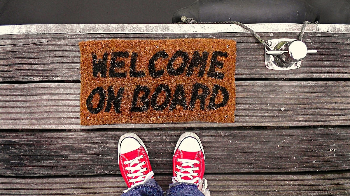 """Person stands on boat dock next to """"Welcome on board"""" welcome mat"""