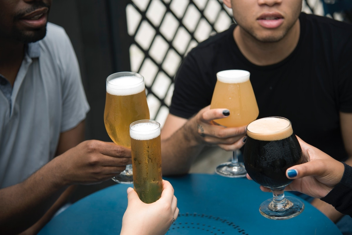 Four people with beer glasses sit around a table and give cheers