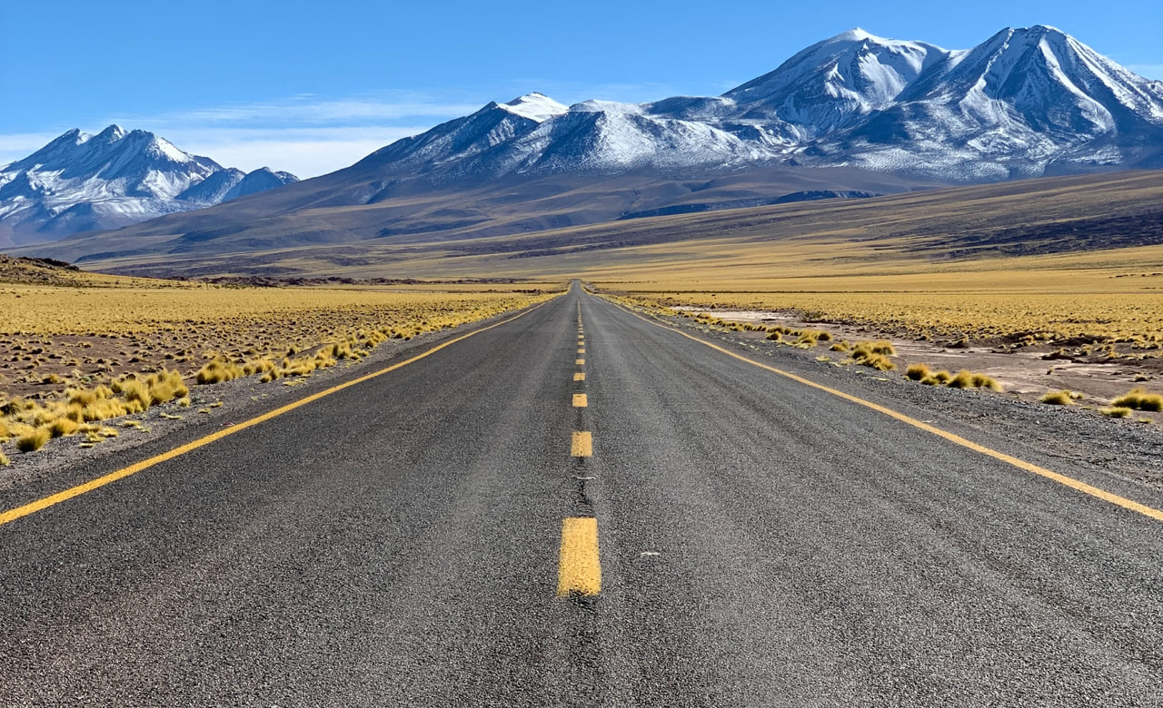 View of a highway with no cars on it in first person perspective with snow capped mountains in thedistance