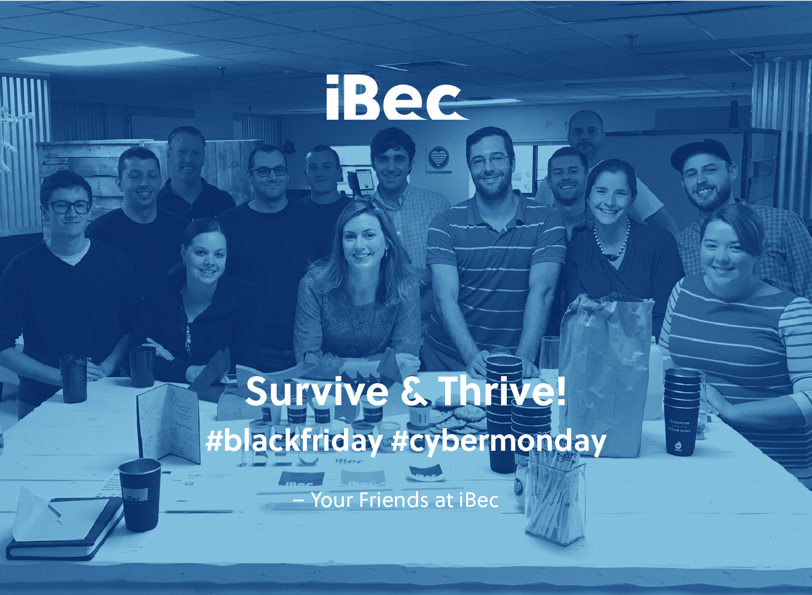 iBec team gathered around a white table, facing the camera and smiling