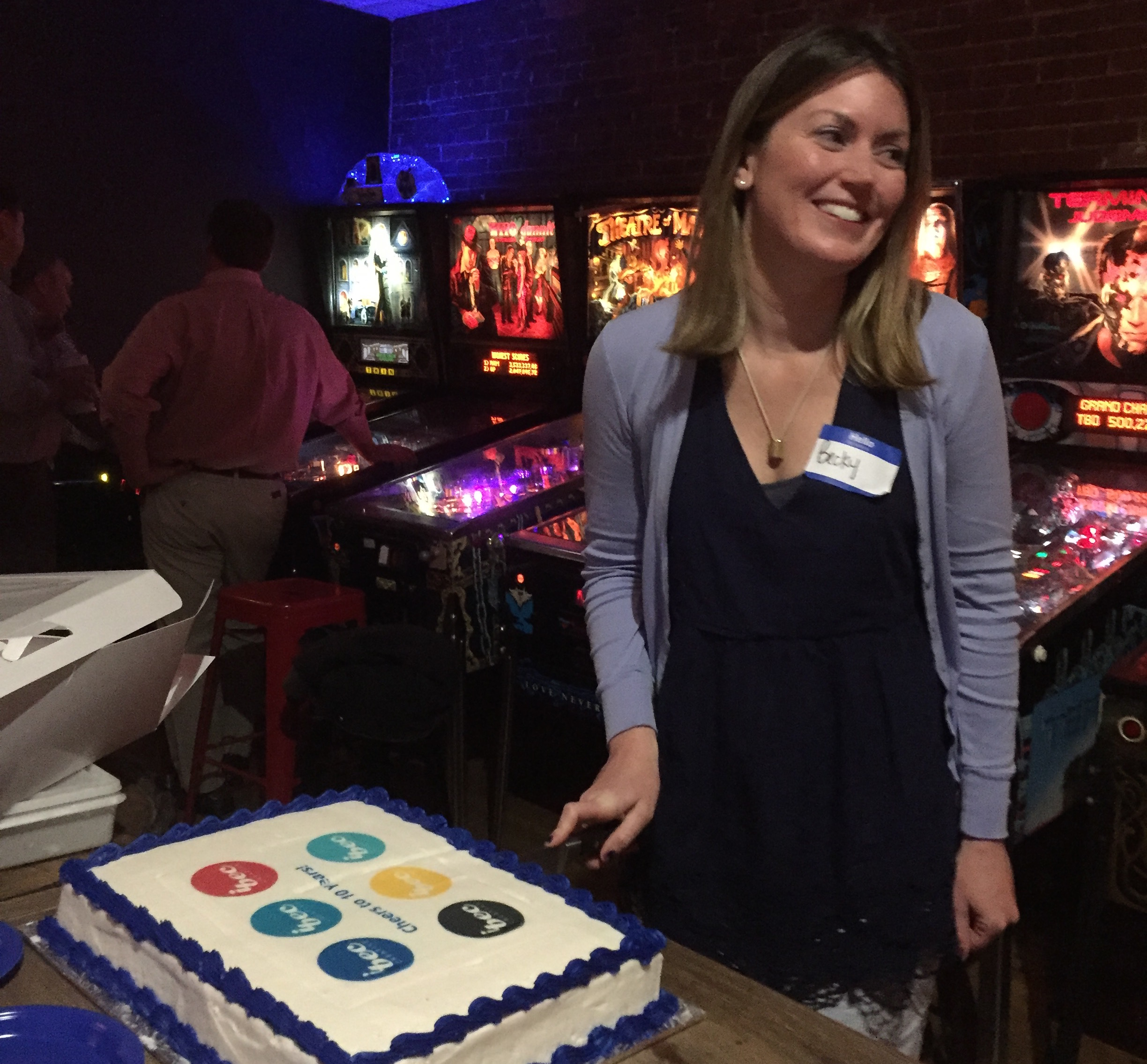 At local Arcade bar, Arcadia, iBec Founder, Becky McKinnell, makes the first cut into the cake to celebrate iBec's 10 year anniversary.