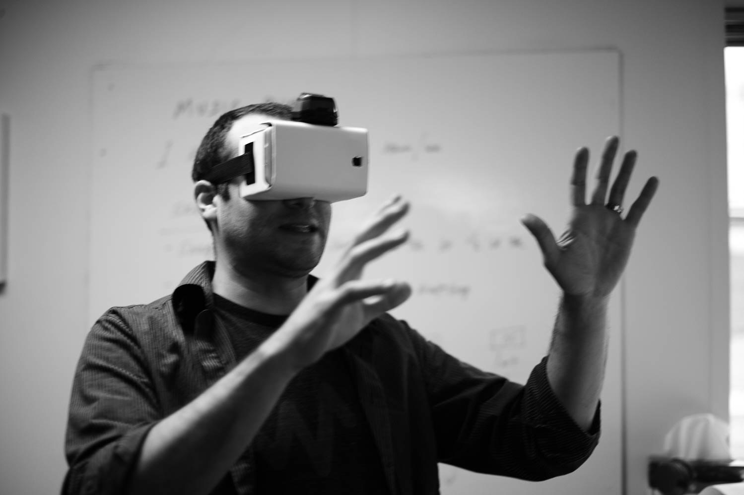 iBec designer, Matt Smith, holds his hands out in front of him while using Google's cardboard VR headset