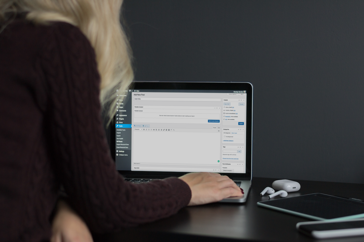A woman seated at a desk is facing her laptop. The laptop is open to the WordPress page editing screen.