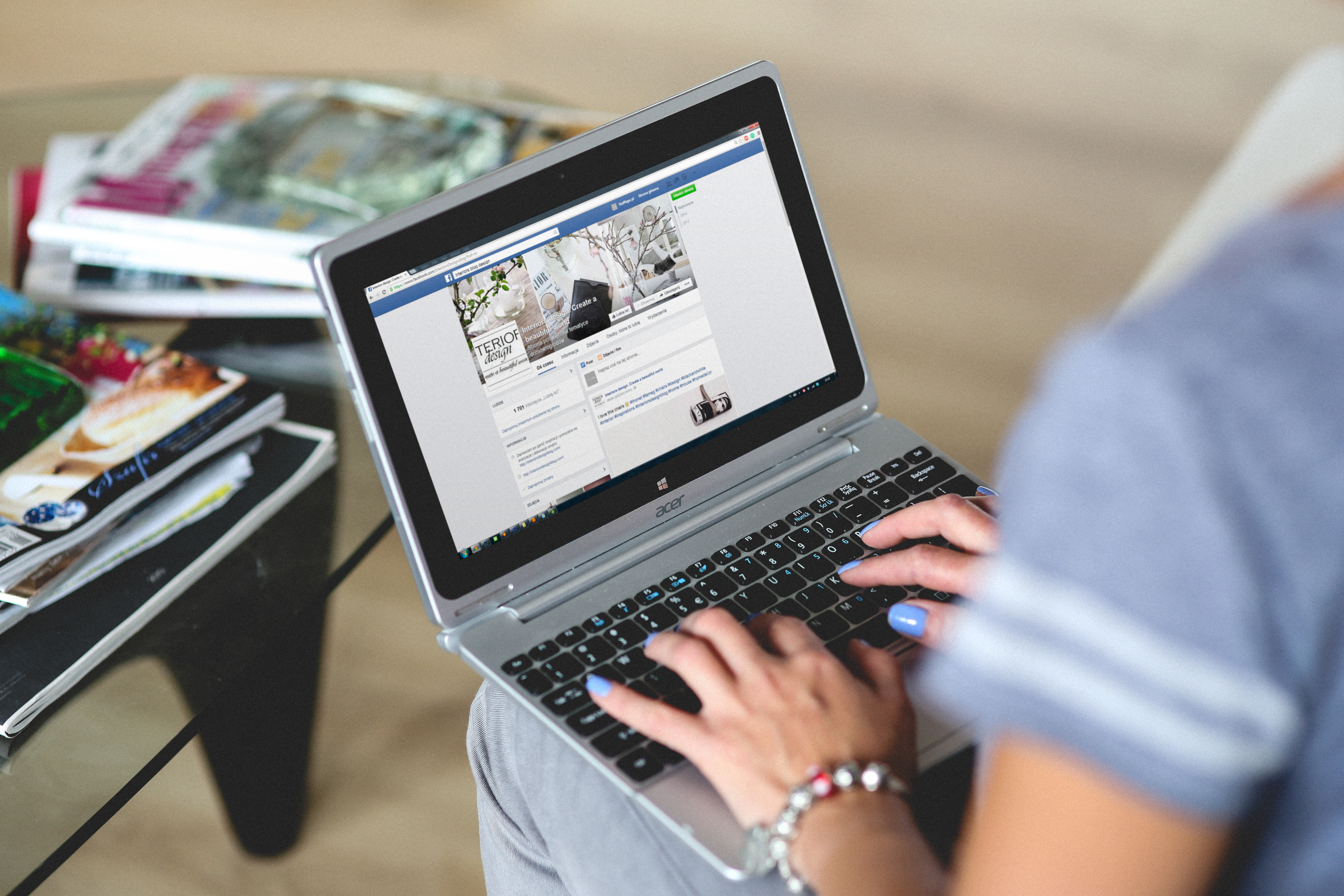 Over the shoulder view of person holding laptop and scrolling through Facebook
