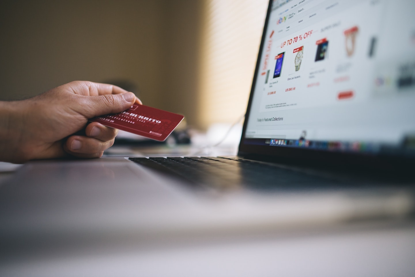 Person holding credit card while shopping on ecommerce website