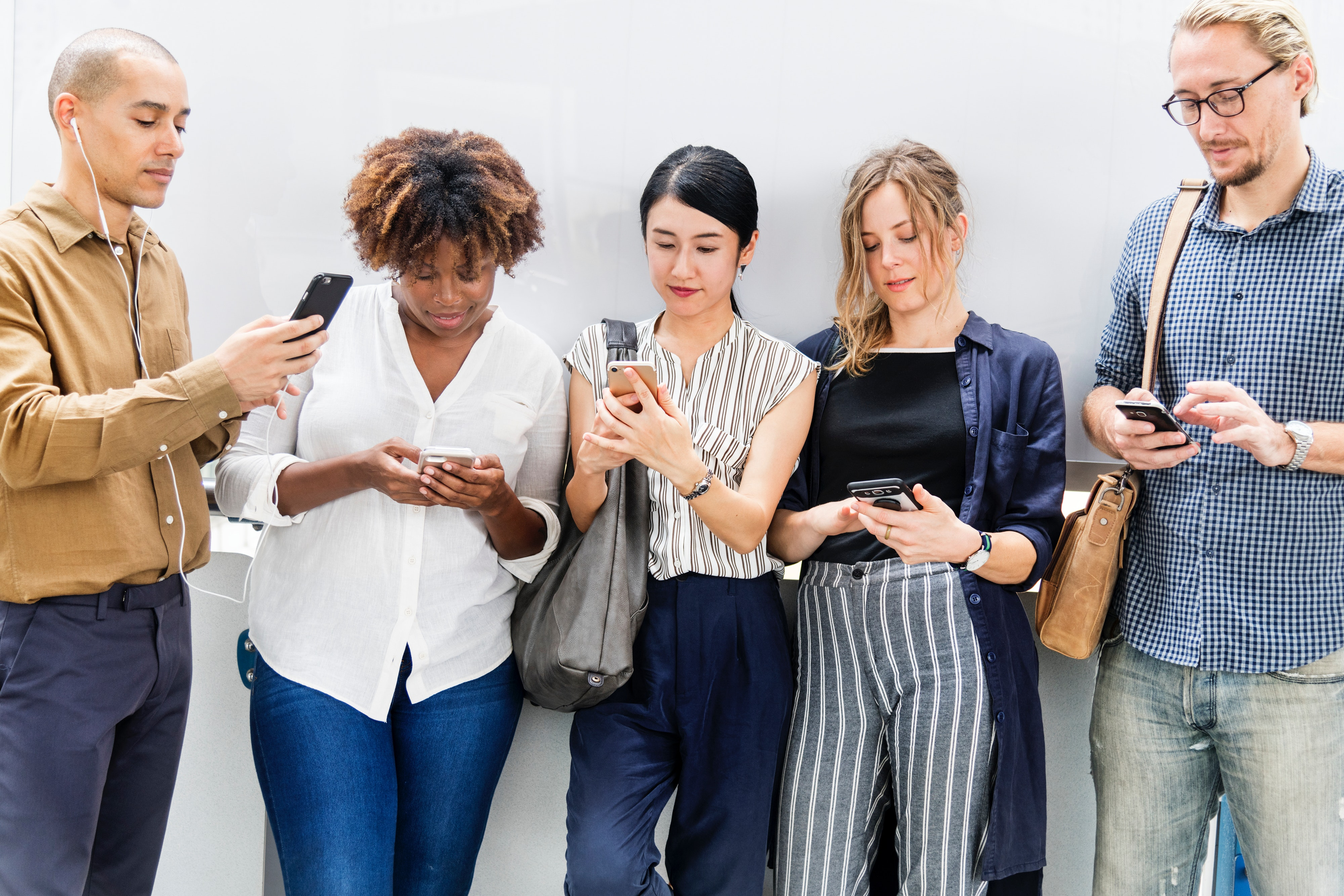 Five adults standing side by side while looking at their phones