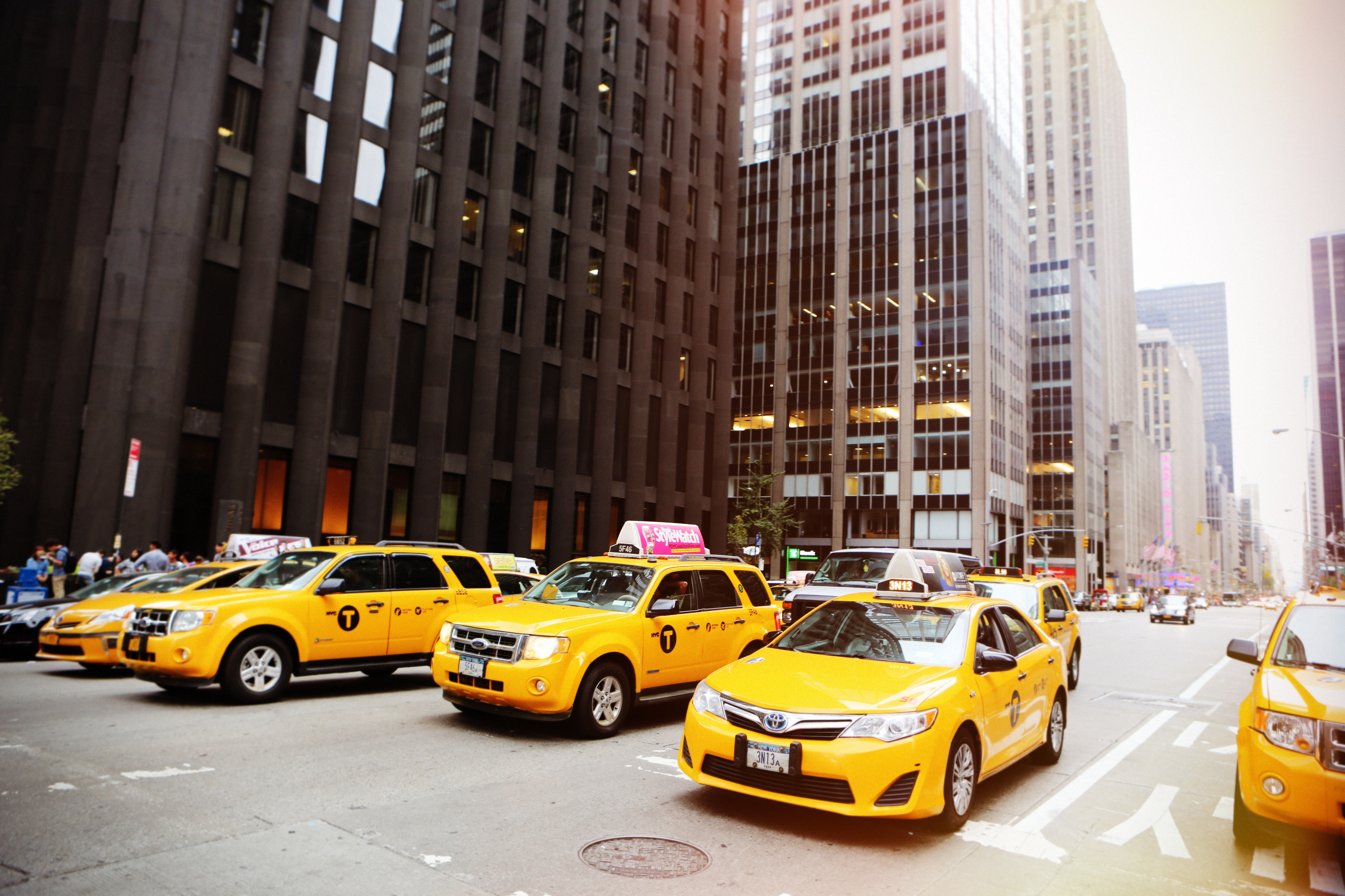 Yellow taxi cabs lined up at a stoplight in the city