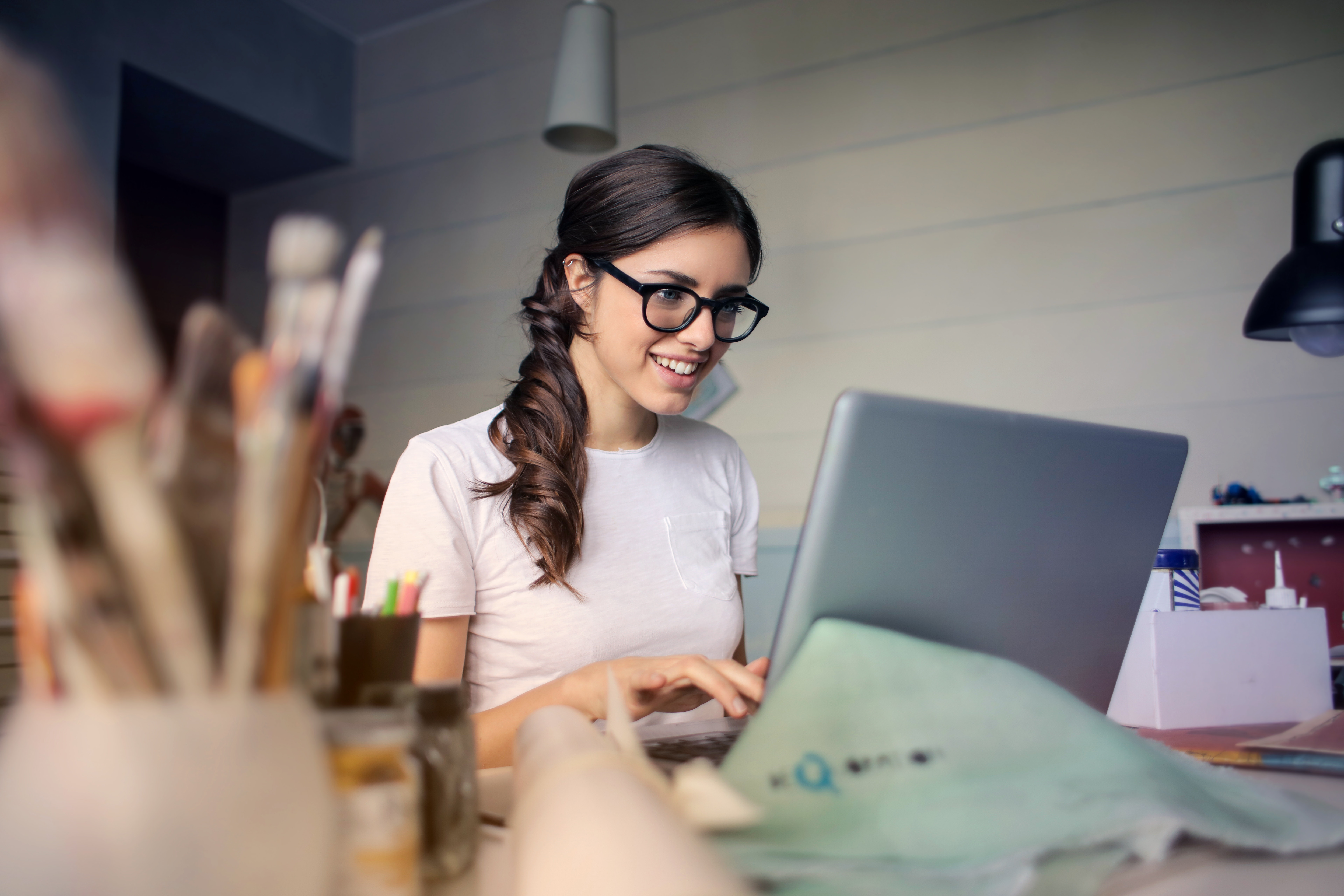 Person on laptop in a studio smiling