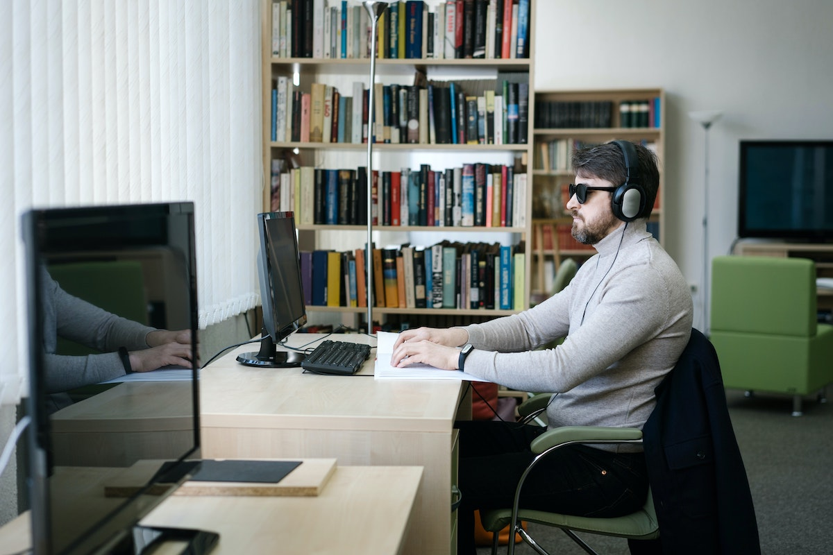 Man wearing sunglasses and headphones reads braille at the computer in a library.