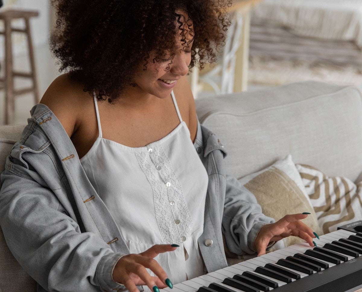 A woman with curly brown hair, a jean jacket and long fingernails painted metallic green is sitting cross legged on a gray linen couch while playing a black and white electronic keyboard and smiling.