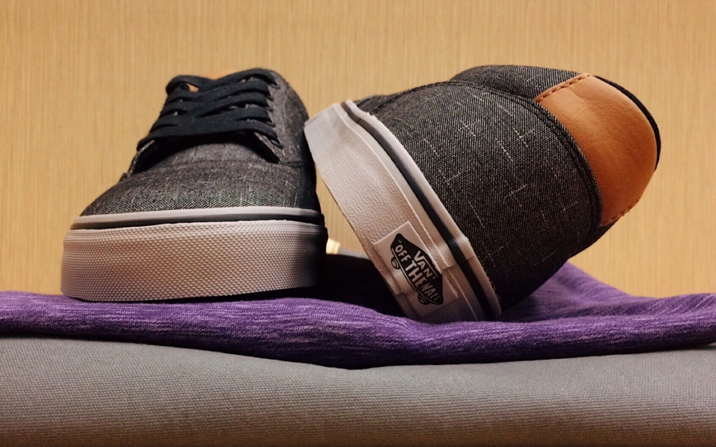 A pair of canvas grey vans with white soles and black shoelaces on top of a folded purple heathered shirt and grey canvas jeans