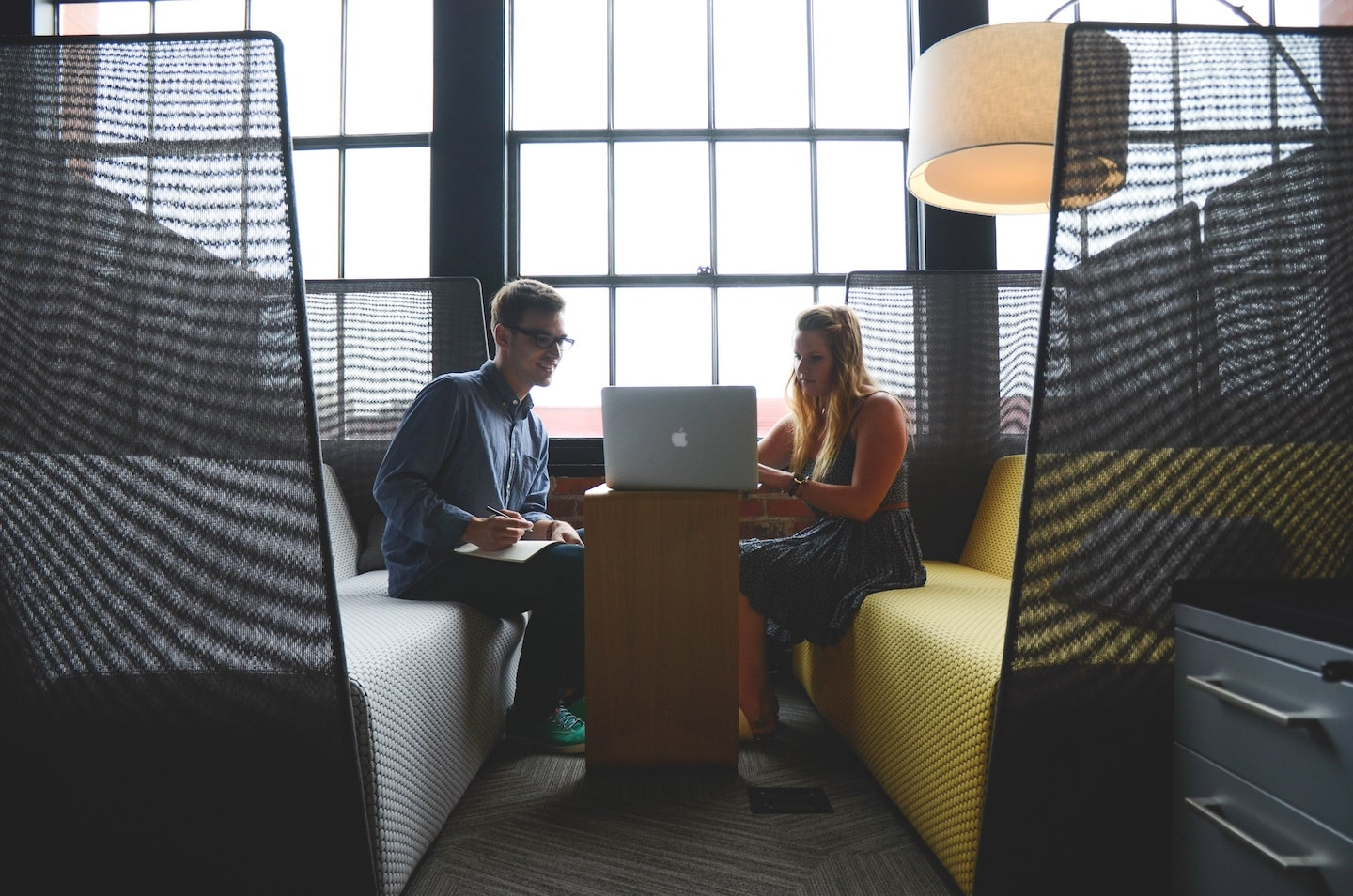 Two people sit together looking at the computer in a colorful, modern office setting with large windows