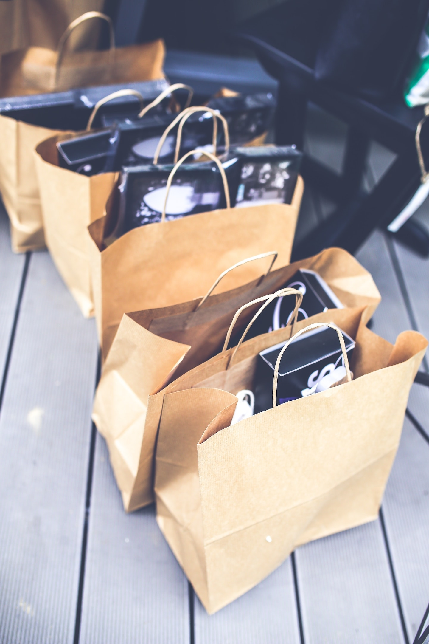 Five brown paper shopping bags filled with miscellaneous items lined up on the floor