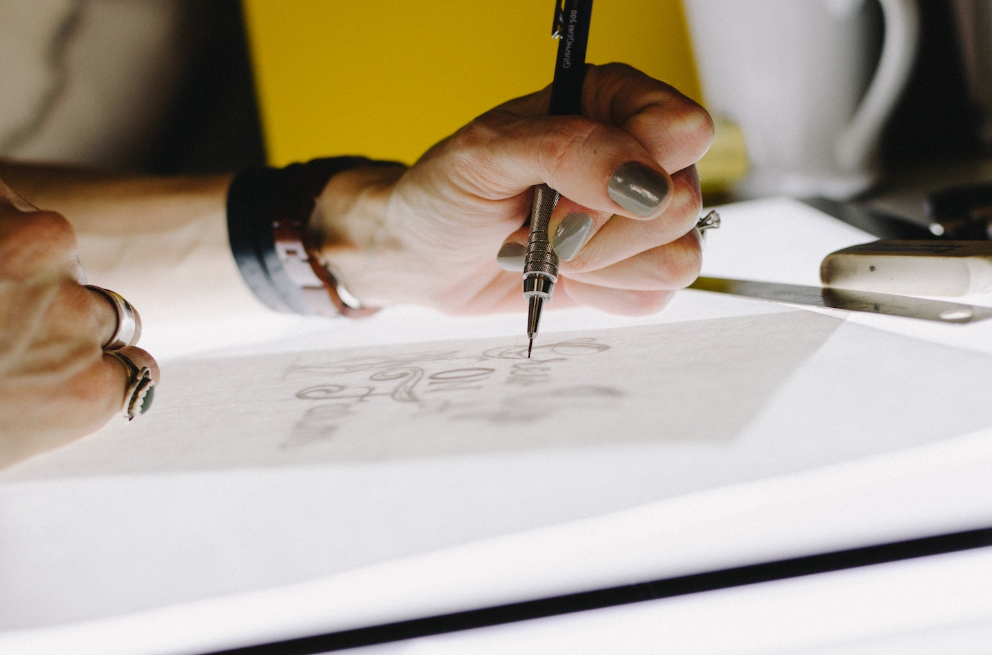 A close-up of someone tracing a graphic on a backlit surface.