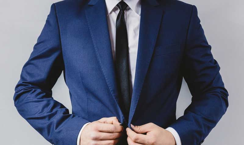 A formal dressed person wearing a white button up shirt and thin, black tie buttons the top button on their navy suit jacket