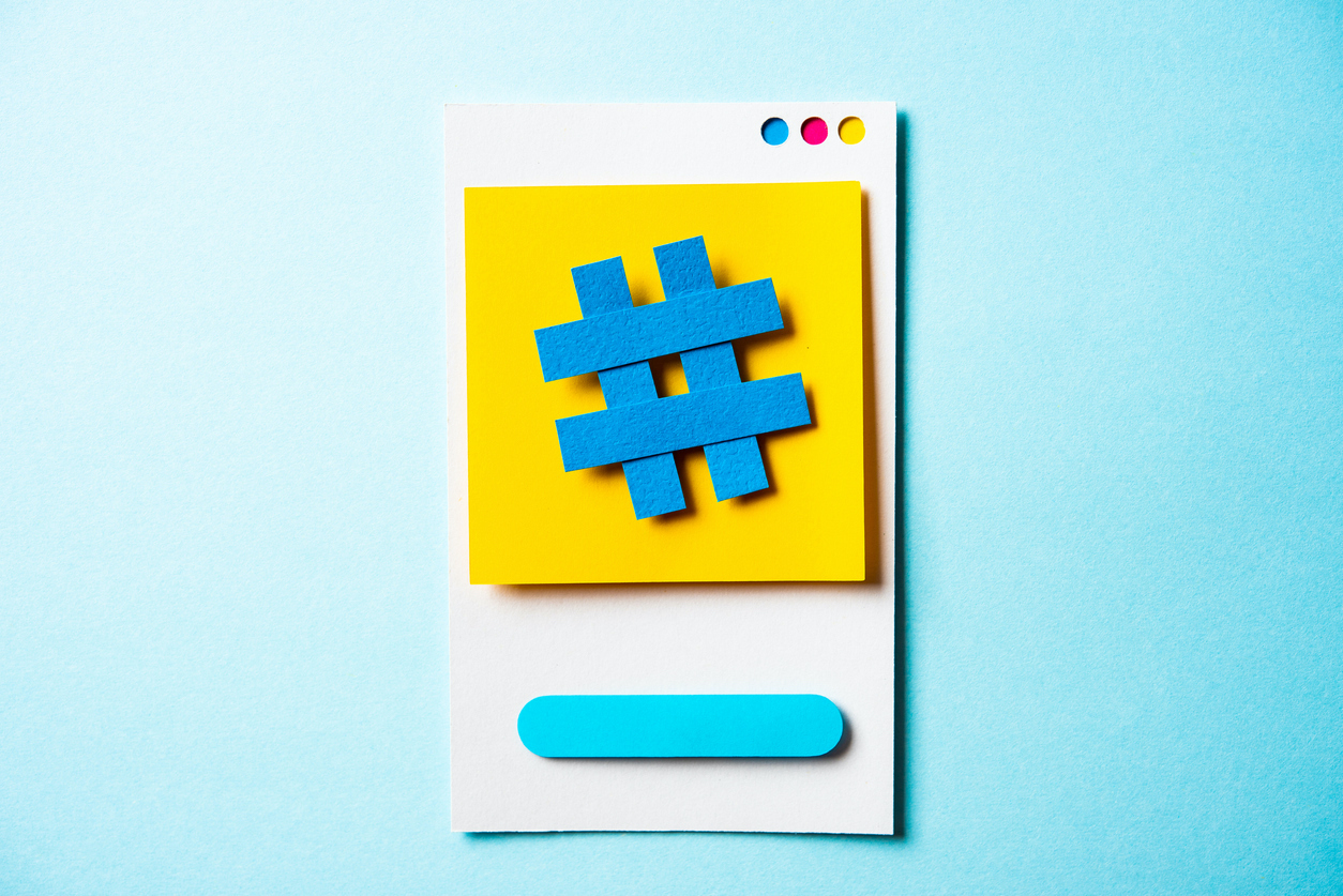 Paper phone against a light blue background. Blue paper hashtag symbol against a yellow paper screen.