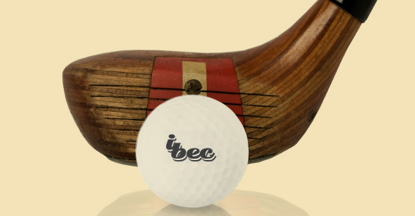 Close-up of an iBec golf ball in front of a golf club