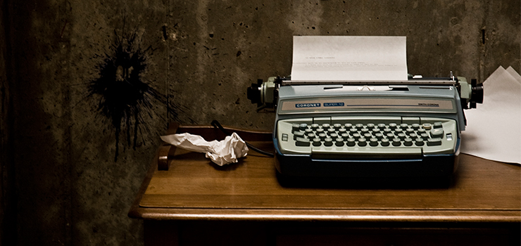 typewriter on a desk with a crumpled piece of paper next to it in a dark room